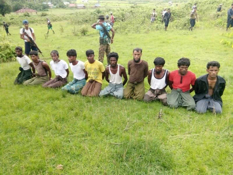 Ten Rohingya men with their hands bound kneel as members of the Myanmar security forces stand guard in Inn Din village