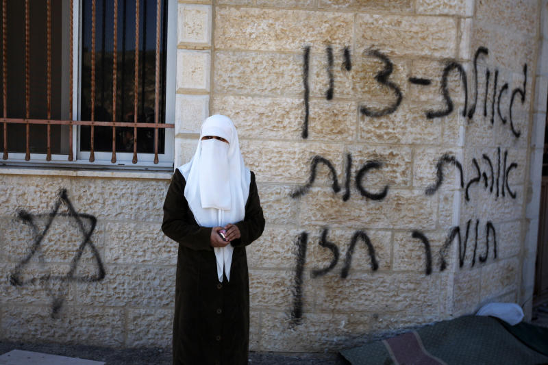 "A Palestinian woman stands next to a vandalized mosque in the West Bank village of Burka, near Ramallah, Thursday, Oct. 10, 2013. The Hebrew graffiti reads, ""Redemption of Zion, I love Tomer Hazan."" Hazan was an Israeli soldier killed by a Palestinian in a West Bank village in September 2013. Palestinian residents of the village said that masked Jewish settlers torched three cars and defaced a mosque during an overnight attack. (AP Photo/Majdi Mohammed)"