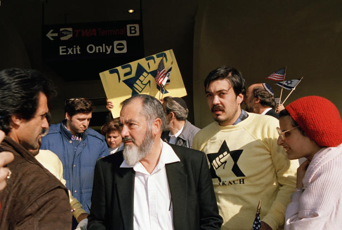 """FILE - In this Oct. 27, 1988, photo, leader and co-founder of the Jewish Defense League, Brooklyn-born Rabbi Meir Kahane, is joined by supporters shortly after arriving at John F. Kennedy Airport in New York. In the 1980s, Kahane's violent anti-Arab ideology was considered so repugnant that Israel banned him from parliament and the U.S. listed his party as a terrorist group. Today, his disciples march through the streets of Jerusalem and other cities by the hundreds, chanting """"Death to Arabs"""" and attacking any that cross their path. (AP Photo/Susan Ragan, File)"""