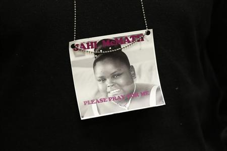 A photograph of 13-year-old Jahi McMath is seen on a necklace in Oakland