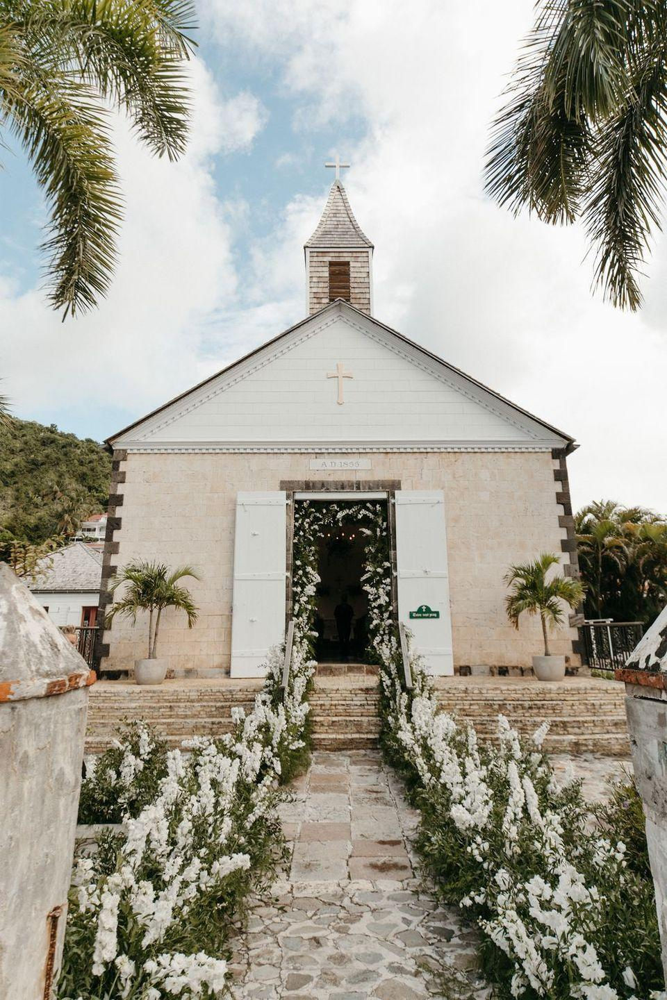 """<p>An aisle looks like it goes on for days when it has a direct correlation with the other arrangements and archways in the space, from the entry of the church to your <a href=""""https://www.harpersbazaar.com/wedding/planning/g30031551/wedding-arch-ideas/"""" rel=""""nofollow noopener"""" target=""""_blank"""" data-ylk=""""slk:wedding arch"""" class=""""link rapid-noclick-resp"""">wedding arch</a> or altar. That continuity guides guests' eyes throughout the space, and exudes abundance without feeling frivolous. This look transforms your ceremony space by drawing the eye from one moment to the next. Trust us: there's nothing more romantic than a far-as-the-eye-can-see aisle, especially when it's lined with gestural blooms and wispy grasses.</p><p>Pictured: <a href=""""https://www.harpersbazaar.com/wedding/photos/a29846496/devon-windsor-wedding/"""" rel=""""nofollow noopener"""" target=""""_blank"""" data-ylk=""""slk:Devon Windsor and Johnny Barbara's wedding in St. Barths"""" class=""""link rapid-noclick-resp"""">Devon Windsor and Johnny Barbara's wedding in St. Barths</a>. Planning by <a href=""""https://mindyweiss.com/"""" rel=""""nofollow noopener"""" target=""""_blank"""" data-ylk=""""slk:Mindy Weiss"""" class=""""link rapid-noclick-resp"""">Mindy Weiss</a>; Floral design by <a href=""""https://www.bowsandarrowsflowers.com/#!/H_O_M_E_"""" rel=""""nofollow noopener"""" target=""""_blank"""" data-ylk=""""slk:Bows & Arrows"""" class=""""link rapid-noclick-resp"""">Bows & Arrows</a>.</p>"""