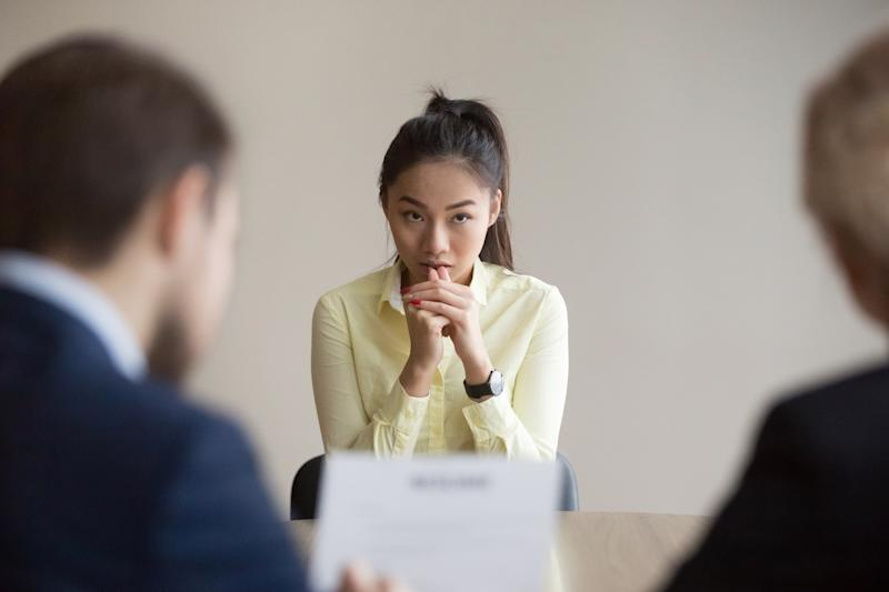 Nervous young Asian job applicant wait for recruiters question during interview in office, worried intern or trainee feel stressed applying for open position, meeting with hr managers. Hiring concept