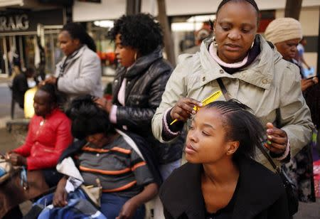 Hairdressers attend to clients in downtown Johannesburg