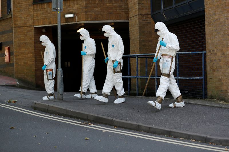 Forensic officers are pictured near the scene of reported multiple stabbings in Reading