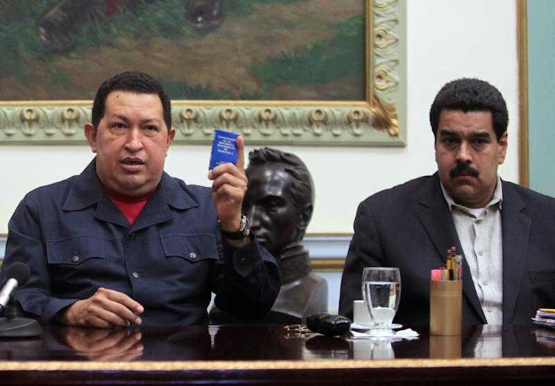 "FILE - In this Dec. 8, 2012, file photo released by Miraflores Press Office, Venezuela's President Hugo Chavez, left, holds up a copy of the Venezuelan national constitution as his Vice President Nicolas Maduro looks on during a televised speech at Miraflores presidential palace in Caracas, Venezuela. Chavez has suffered ""new complications"" following his cancer surgery in Cuba, Maduro said Sunday, Dec. 30, 2012, describing the Venezuelan leader's condition as delicate. (AP Photo/Miraflores Press Office, Marcelo Garcia, file)"
