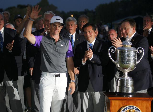 Rory McIlroy of Northern Ireland celebrates with PGA officials when presented with the Wanamaker Trophy after winning the 2014 PGA Championship at Valhalla Golf Club in Louisville, Kentucky, August 10, 2014. REUTERS/John Sommers II (UNITED STATES - Tags: SPORT GOLF)