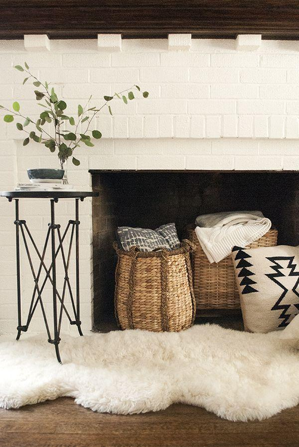 """<p>Warm up a non-working fireplace with cozy accessories such as <a href=""""https://www.elledecor.com/design-decorate/trends/g3329/throw-pillows/"""" rel=""""nofollow noopener"""" target=""""_blank"""" data-ylk=""""slk:pillow-and-throw-filled baskets"""" class=""""link rapid-noclick-resp"""">pillow-and-throw-filled baskets</a>, a plush sheepskin rug and a little branch of eucalyptus in a vase, as <a href=""""http://www.cocokelley.com/2015/10/how-to-style-faux-fireplace-fall/"""" rel=""""nofollow noopener"""" target=""""_blank"""" data-ylk=""""slk:Coco Kelley"""" class=""""link rapid-noclick-resp"""">Coco Kelley</a> did in this vignette. An added benefit: Easy access to warm blankets on cold evenings. </p>"""