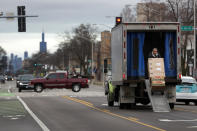 A delivery man unloads his truck on what is usually a busy Madison Ave. in the Village of Oak Park, Ill., Friday, March 20, 2020. There are at least three confirmed cases of COVID-19 in Oak Park, just nine miles from downtown Chicago, where the mayor has ordered residents to shelter in place. With so few tests available, surely there are others, says Tom Powers, spokesman for the village of about 52,000 in a metropolitan area with millions. (AP Photo/Charles Rex Arbogast)