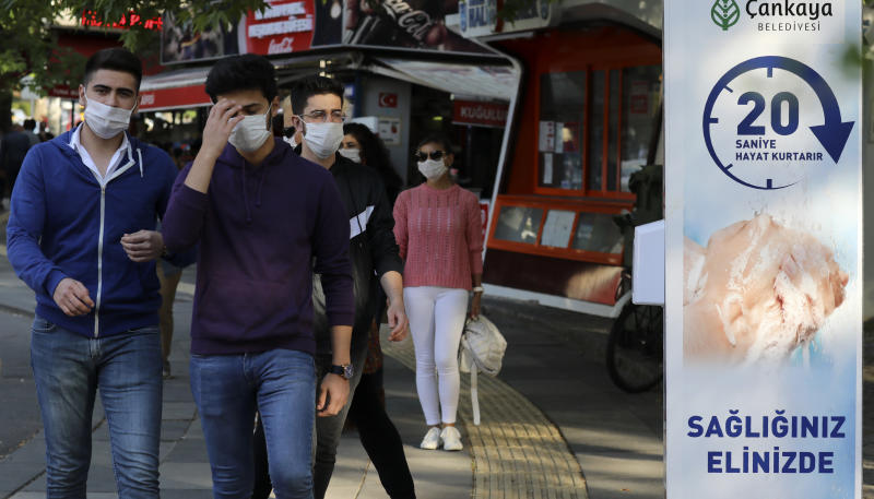 "People wearing face masks to protect against the coronavirus, pass a sign that reads: ""washing hands for 20 seconds saves your life"", at the entrance of a public garden, in Ankara, Turkey, Sunday, June 14, 2020. Turkey's President Recep Tayyip Erdogan has revealed Tuesday new plans to ease restrictions in place to curb the spread of the coronavirus, including the July 1 reopening of theaters, cinemas and other entertainment centers. (AP Photo/Burhan Ozbilici)"