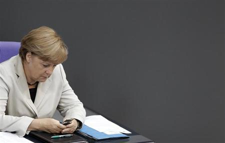 German Chancellor Angela Merkel looks at her mobile phone during a session of the Bundestag, German lower house of parliament, at the Reichstag in Berlin September 12, 2012.