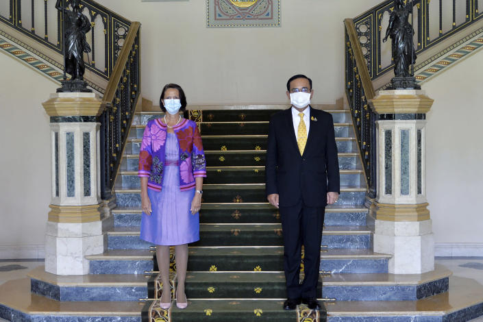 In this photo released by Government Spokesman Office, United Nations Special Envoy to Myanmar Christine Schraner Burgener, left, and Thailand's Prime Minister Prayuth Chan-ocha pose for a photo prior to a meeting at Government House in Bangkok, Thailand, Friday, May 14, 2021. (Government Spokesman Office via AP)