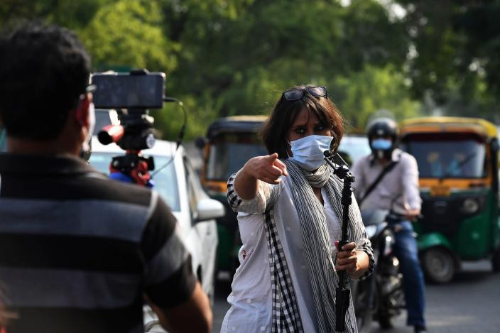 In this photograph taken on June 12, 2020 journalist Barkha Dutt (C) reports from Guru Teg Bahadur (GTB) hospital in New Delhi, after authorities eased restrictions imposed as a preventive measure against the spread of the COVID-19 coronavirus. - Dutt has driven the length and breadth of India -- 23,000 kilometers over more than 100 days -- to tell how the country's army of poor have suffered in the coronavirus pandemic. (Photo by Prakash SINGH / AFP) / To go with AISHAWARYA KUMAR story (Photo by PRAKASH SINGH/AFP via Getty Images)