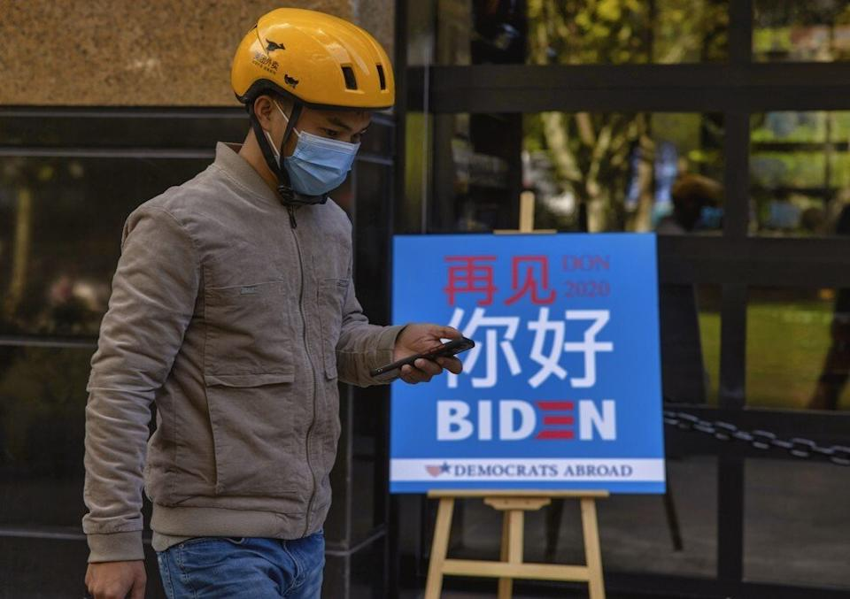 A man walks past a board inviting people to an election watch party hosted by Democrats Abroad in Shanghai. Photo: EPA-EFE