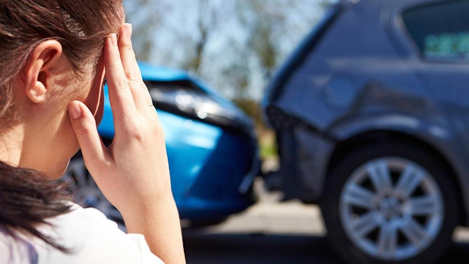 Stressed Driver Sitting At Roadside After Traffic Accident looking at the damage.