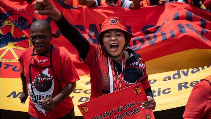 """A woman at a protest in Johannesburg standing next to man and a crowd in the background. The people are wearing all red. The woman has her fist in the air and appears to be shouting. She is carrying a banner which says: """"decent work equals fair income."""""""