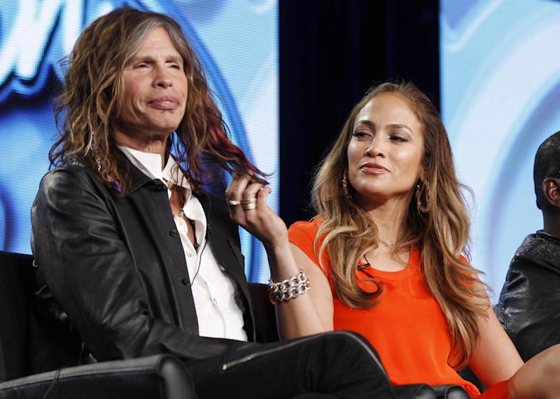 """FILE - In this Jan. 8, 2012 file photo, American Idol judge Jennifer Lopez, right, plays with the hair of fellow judge Steven Tyler of Aerosmith as they participate in the American Idol panel at the Fox Broadcasting Company Television Critics Association Winter Press Tour in Pasadena , Calif. Tyler is mum on whether he or Jennifer Lopez will return to the judging panel on """"American Idol"""" next year, but the rocker says he has loved the experience of sitting next to her. """"She's a sexy beast,"""" Tyler said in a phone interview on Monday, May 21. """"I feed off that female energy with her."""" (AP Photo/Danny Moloshok, file)"""