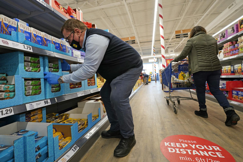 "In this Thursday, Feb. 4, 2021 photo, grocery supervisor Joseph Lupo, left, arranges cookies in the shelves at the Lidl food market in Lake Grove, N.Y., where he works after getting the first dose of the COVID-19 vaccination earlier in the day. Lupo, who fell ill with the virus in March, was elated to get his first vaccine dose. ""I never ever want to get COVID again, or see anybody else get it,"" said Lupo, 59. (AP Photo/Kathy Willens)"