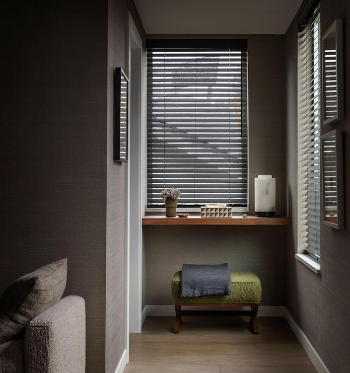 This nook in the primary bedroom is a showcase for the muted, nature-inspired color palette Paquette chose for his home, as evidenced by the sage green ottoman and the warm wood flooring.