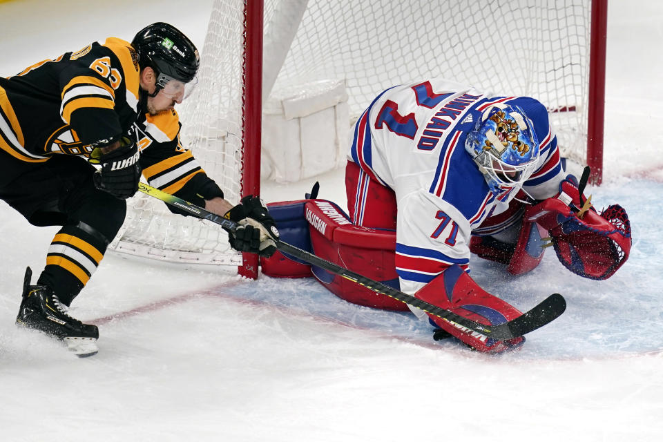 New York Rangers goaltender Keith Kinkaid (71) pounces on the puck as he makes a save against Boston Bruins center Brad Marchand (63) without his stick during the second period of an NHL hockey game, Saturday, May 8, 2021, in Boston. (AP Photo/Charles Krupa)
