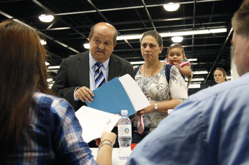 In this June 13, 2012 file photo, Jose Canales, left, talks to a recruiter as he is accompanied by his wife, Magdel, and daughter Alexamarie at a job fair expo in Anaheim, Calif. A private survey released Thursday, July 5, 2012, shows U.S. businesses increased hiring in June, suggesting the job market could be recovering after three sluggish months. (AP Photo/Jae C. Hong, File)