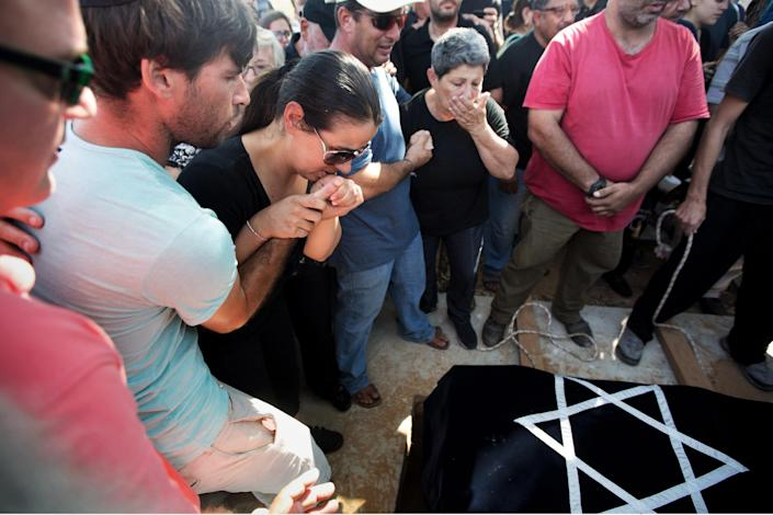 Israelis Gila (2nd left) and Doron (left) Tragerman mourn over the coffin of their son Daniel during his funeral in the Israeli village of Yevul located near the border with Gaza Strip on August 24, 2014 (AFP Photo/Menahem Kahana)