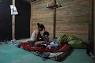 Colombian coca leaf collector Karen Palacios, 20, gets ready with her daughter for her work shift at a coca field -- she has been doing this work since she was a teenager (AFP/Raul ARBOLEDA)