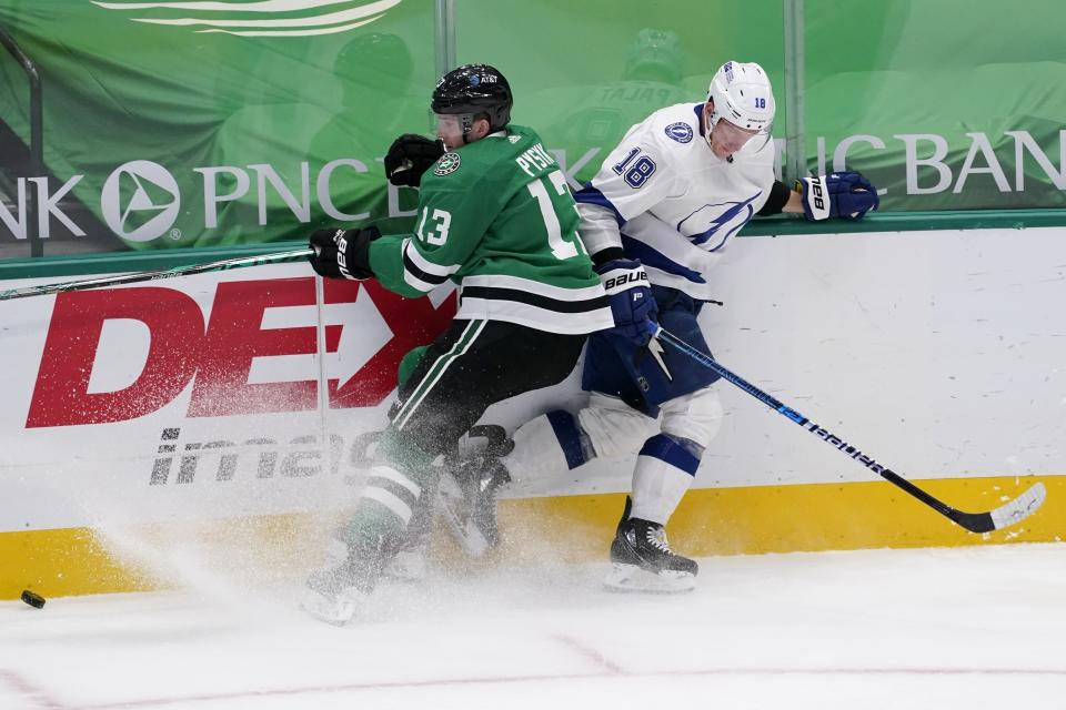 Dallas Stars' Mark Pysyk (13) and Tampa Bay Lightning's Ondrej Palat (18) compete for control of a loose puck in the first period of an NHL hockey game in Dallas, Tuesday, March 2, 2021. (AP Photo/Tony Gutierrez)