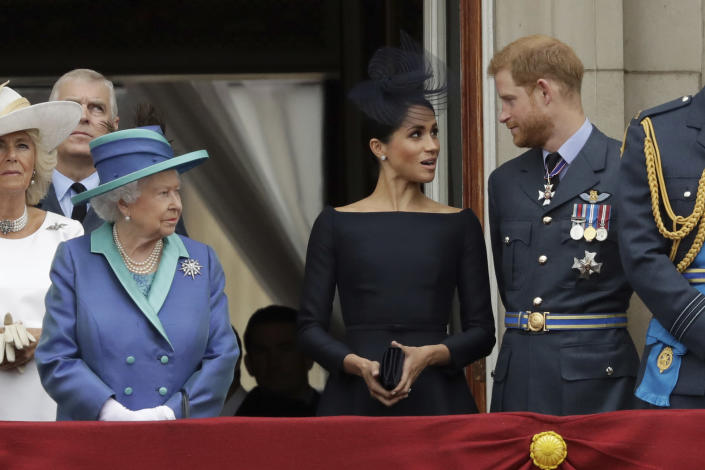 FILE - In this Tuesday, July 10, 2018 file photo Britain's Queen Elizabeth II, Meghan the Duchess of Sussex and Prince Harry stand on a balcony to watch a flypast of Royal Air Force aircraft pass over Buckingham Palace in London. The timing couldn't be worse for Harry and Meghan. The Duke and Duchess of Sussex will finally get the chance to tell the story behind their departure from royal duties directly to the public on Sunday, March 7, 2021, when their two-hour interview with Oprah Winfrey is broadcast. (AP Photo/Matt Dunham, File)