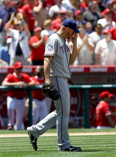 Texas Rangers starting pitcher Matt Harrison wipes his face after giving up a run to the Los Angeles Angels during the fifth inning of a baseball game in Anaheim, Calif., Sunday, June 3, 2012. (AP Photo/Chris Carlson)