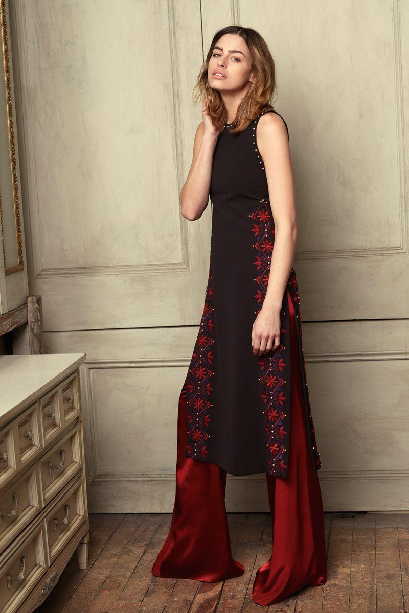 A model wearing red pants and a black sleeveless dress