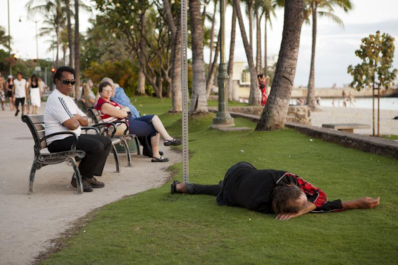 As tourists watch the sun go down, a man sleeps near Waikiki Beach, Friday, May 13, 2011 in Honolulu.  Honolulu is currently grappling with one of nation's most serious homeless challenges as the city prepares to host the Asia Pacific Economic Cooperation conference in November.  Homelessness threatens to mar the perfect picture Hawaii would like to present to those attending APEC.  (AP Photo/Marco Garcia)