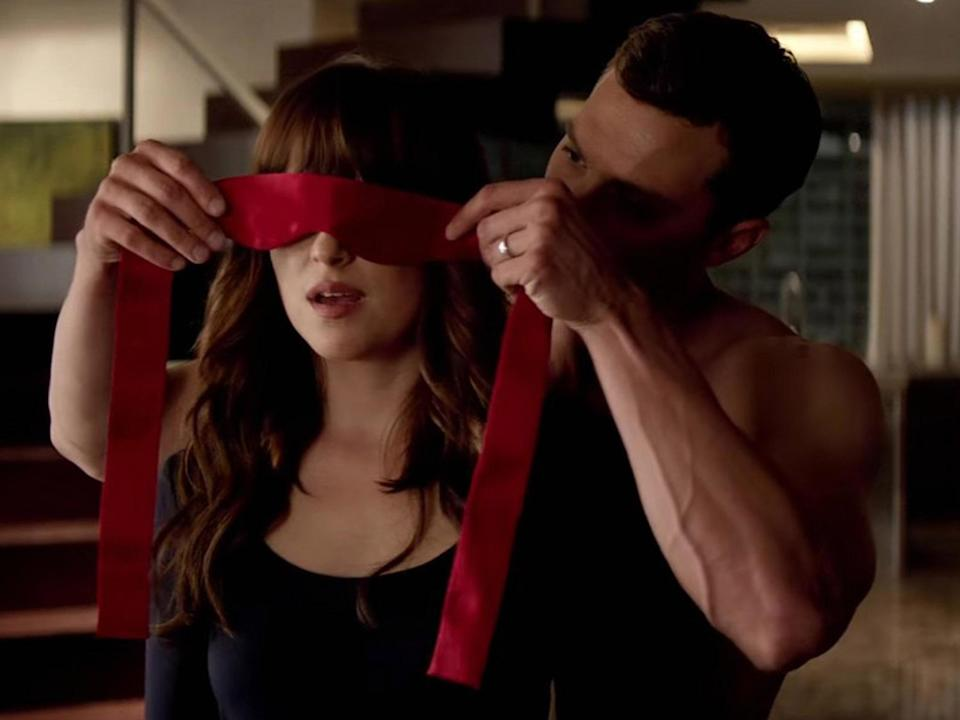 Christian Grey puts Ana Steele in a blindfold in Fifty Shades of Grey: Universal