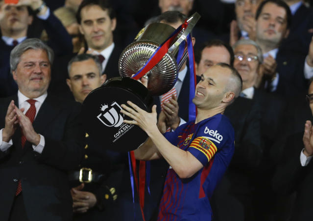 FC Barcelona's Andres Iniesta holds up the trophy as he celebrates during an award ceremony after defeating Sevilla 5-0 in the Copa del Rey final soccer match at the Wanda Metropolitano stadium in Madrid, Spain, Saturday, April 21, 2018. (AP Photo/Francisco Seco)
