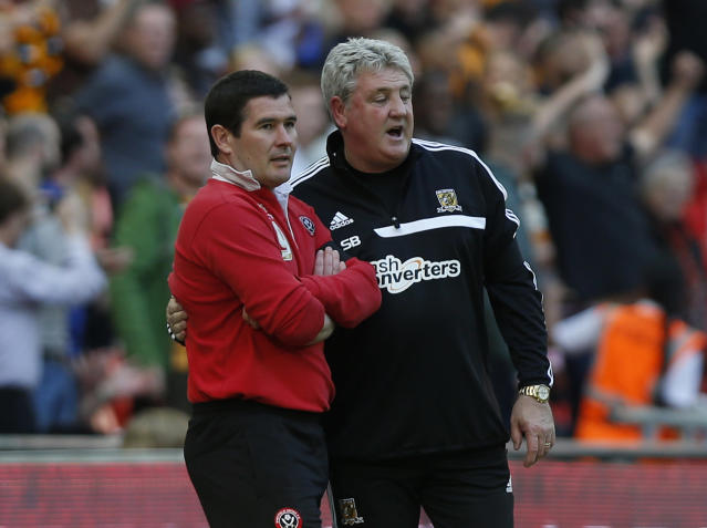 Hull City's manager Steve Bruce, right, consoles Sheffield United's manager Nigel Clough as his team is about to win near the end of their English FA Cup semifinal soccer match at Wembley Stadium in London, Sunday, April 13, 2014. (AP Photo/Sang Tan)
