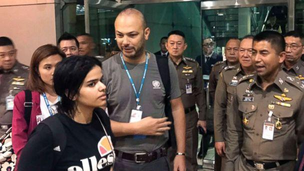 PHOTO: In this Jan. 7, 2019, file photo released by the Immigration Bureau, Saudi woman Rahaf Mohammed Alqunun, foreground, walks by Chief of Immigration Police Maj. Gen. Surachate Hakparn, right, before leaving the Suvarnabhumi Airport in Bangkok. (Immigration police via AP, FILE)