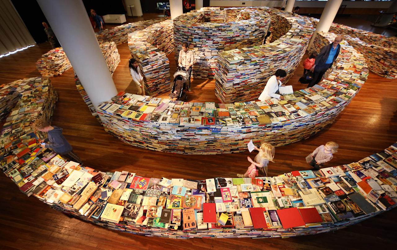 LONDON, ENGLAND - JULY 31:  Visitors enjoy the 'aMAZEme' labyrinth made from books at The Southbank Centre on July 31, 2012 in London, England. Brazilian artists Marcos Saboya and Gualter Pupo used 250,000 books to create the maze which will be on display until August 25, 2012.  (Photo by Peter Macdiarmid/Getty Images)