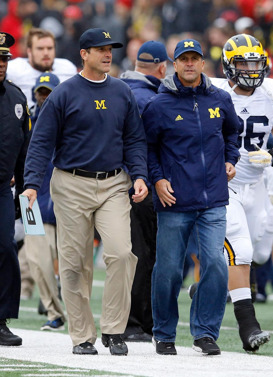 Michigan coach Jim Harbaugh, left, walks off the field with his brother, Ravens coach John Harbaugh, at the end of the first half of U-M's win at Maryland on Oct. 3.