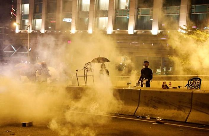 Anti-government demonstrators stand amid tear gas during clashes with police near the Hong Kong Polytechnic University (PolyU) in Hong Kong