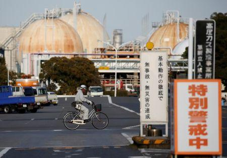 A worker riding a bicycle passes the Fuji Oil Co.'s Sodegaura Refinery in Sodegaura