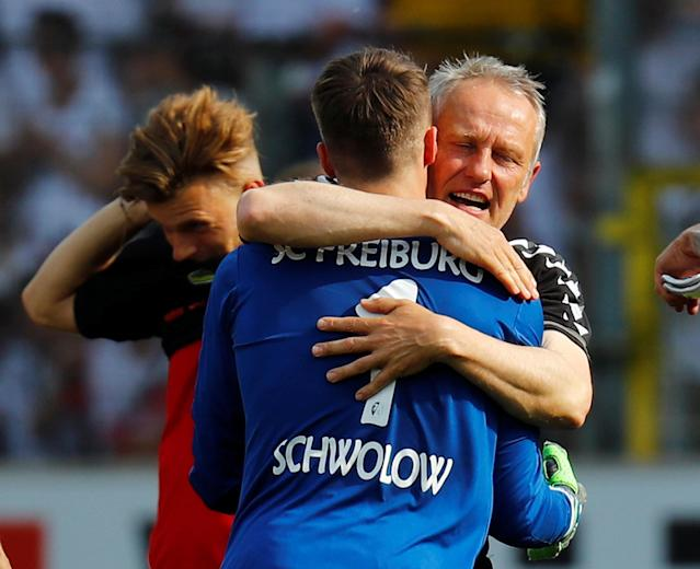 Soccer Football - Bundesliga - SC Freiburg v FC Augsburg - Schwarzwald-Stadion, Freiburg, Germany - May 12, 2018 SC Freiburg coach Christian Streich celebrates with Alexander Schwolow after the match after staying in the Bundesliga REUTERS/Kai Pfaffenbach DFL RULES TO LIMIT THE ONLINE USAGE DURING MATCH TIME TO 15 PICTURES PER GAME. IMAGE SEQUENCES TO SIMULATE VIDEO IS NOT ALLOWED AT ANY TIME. FOR FURTHER QUERIES PLEASE CONTACT DFL DIRECTLY AT + 49 69 650050