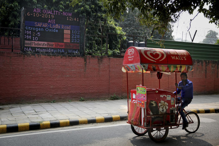 """An ice-cream vendor rides past an air quality level board outside India Meteorological Department which shows condition of air as poor in New Delhi, India, Wednesday, Oct. 16, 2019. The Indian capital's air quality levels have plunged to """"poor,"""" a day after the government initiated stricter measures to fight chronic air pollution. The state-run Central Pollution Control Board's air quality index for New Delhi stood at 299 on Wednesday, about six times the recommended level. (AP Photo/Altaf Qadri)"""