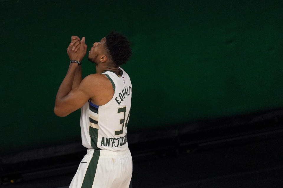 Giannis Antetokounmpo gestures upward with his hands clasped prior to a game.