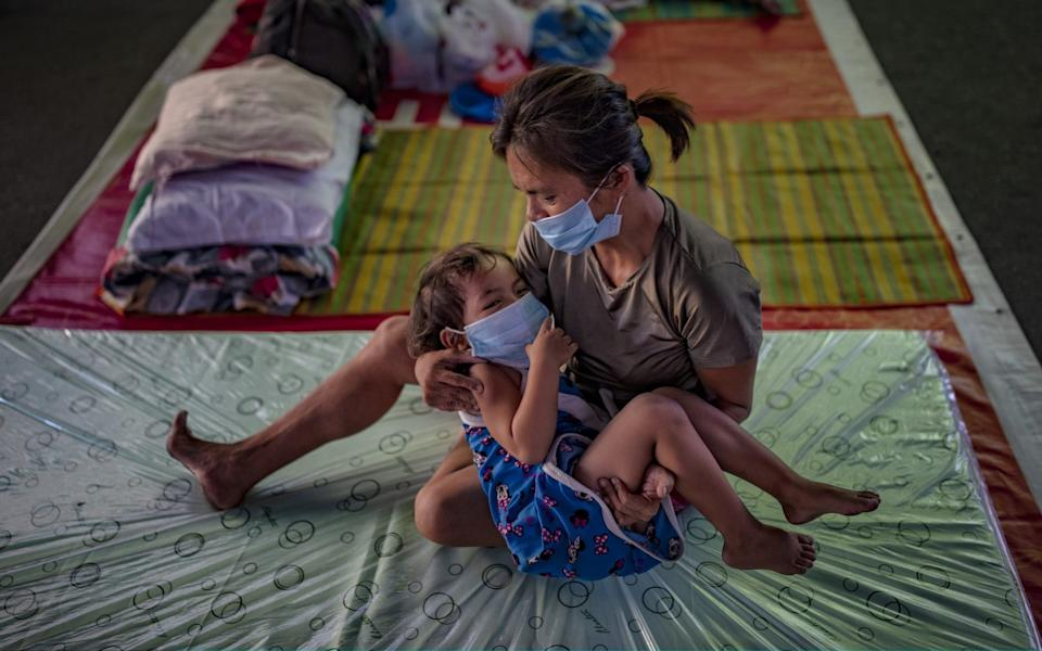 A homeless child and her mother wearing facemasks rest inside a gymnasium converted into a shelter for the homeless who are unable to feed themselves and unable to work because of government lockdown measures - Getty Images AsiaPac