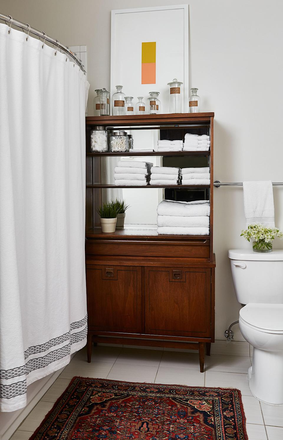 """In Risdon's bathroom, a cabinet purchased on eBay holds towels and vintage apothecary bottles. """"That's had three lives,"""" the designer says, pointing out that he previously used the piece as a bar, and before that as a china cabinet. Like the rest of the apartment, the bathroom displays Risdon's flair for mixing old and new."""