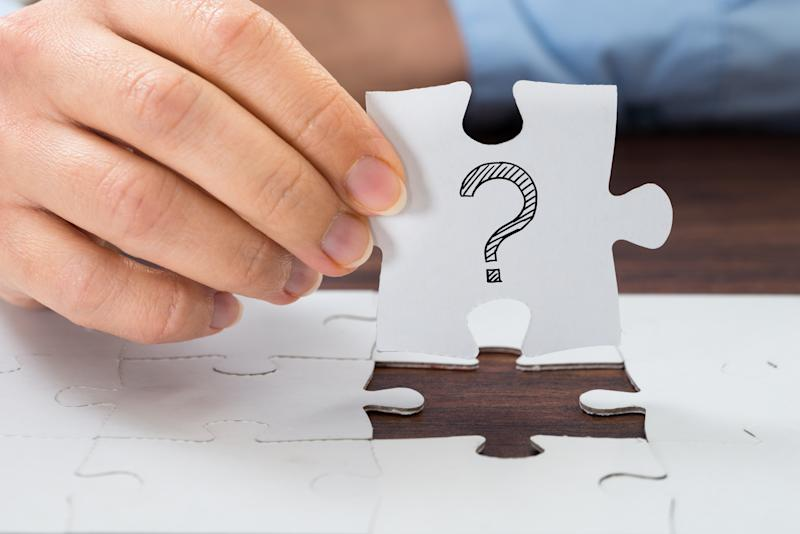 A hand holding up a white puzzle piece, with a large question mark drawn on it in ink.
