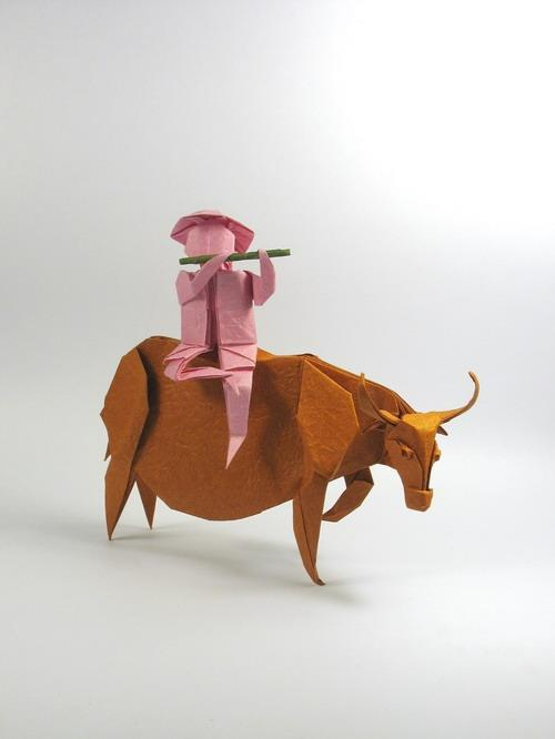 Origami art - Boy on Water Buffalo. I made them for VOG's Year of the Buffalo contest. The boy was folded from one uncut square and the flute was from another paper.