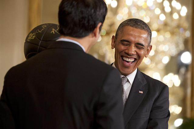 President Barack Obama laughs as Miami Heat coach Erik Spoelstra presents the president with a commemorative trophy during an event in the East Room of the White House in Washington, Tuesday, Jan. 14, 2014, where the president honored the 2013 NBA Champion basketball team. (AP Photo/Jacquelyn Martin)