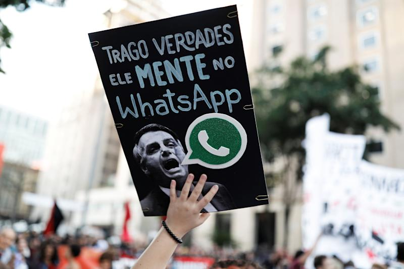 """A woman holds a sign with an image of Jair Bolsonaro that reads """"He lies in WhatsApp,"""" during a protest against then-presidential candidate Bolsonaro in October 2018 in São Paulo, Brazil. (Photo: Nacho Doce / Reuters)"""