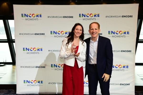 Harry Sommer, incoming president and chief executive officer of Norwegian Cruise Line, presents Leah Egan, Encore Moments winner from Minnesota, with her award at a celebration today in New York City.
