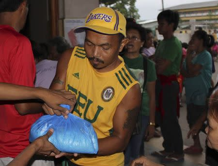 An evacuee received a relief goods after evacuating their homes due to super-typhoon Hagupit in Tacloban city, central Philippines December 5, 2014. REUTERS/Rowel Montes